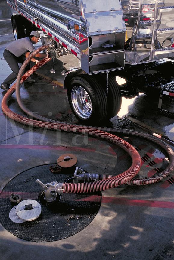 Worker unloading fuel truck to underground storage tank.