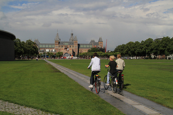 People riding bikes towards the Rijkmuseum, Amsterdam, Holland, Netherlands.