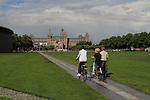 People riding bikes towards the Rijkmuseum, Amsterdam, Holland, Netherlands.