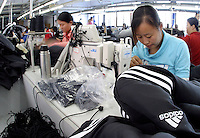 Rolls of workers churn out adidas jackets and pants at the Shengyuan Clothing Factory in Suzhou, Jiangsu Province, China. The factory employs a total of 250 workers that works year-round to fill clothing orders from Adidas and has expanded its operations to a more rural area of the province to meet the demand and cut down labor cost..16-OCT-04