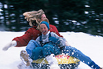 A mother and daughter speed by on a snow tube in the Rocky Mountains, CO