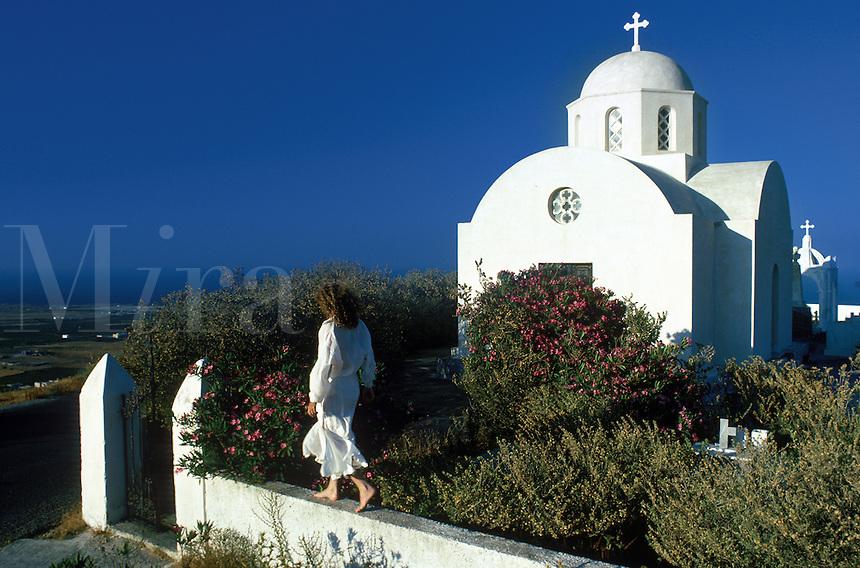 An American tourist strolls along a wall outside a country chapel. Santorini, Greece.