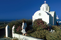 An American tourist strolls along a wall outside a country chapel. Santorini, Greece.
