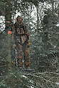 00105-042.13 Bowhunting (DIGITAL) Archer is in tree stand in balsam fir during snow storm.  Hunt, cold, late season, deer, winter.  V7R1