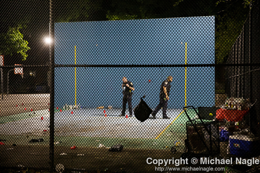 The NYPD investigates a shooting at the Boulevard Houses (NYCHA) on July 17, 2020 in the Brooklyn borough of New York City.  A memorial for Cyril Young, 64, who was found beaten to death in his apartment stands against the handball court.  Photograph by Michael Nagle