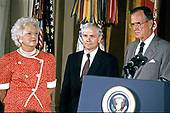 United States President George H.W. Bush and first lady Barbara Bush present the Presidential Citizens Medal to Deputy National Security Advisor Robert Gates during a ceremony in the East Room of the White House in Washington, DC on July 3, 1991. Gates is being honored for his efforts to ensure the success of Operation Desert Shield / Operation Desert Storm and the liberation of Kuwait.<br /> Credit: Ron Sachs / CNP