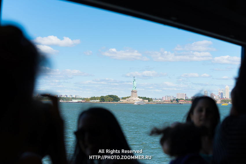 Ferry passengers looking at the Statue of Liberty, New York