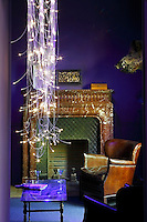 In the purple living room a scintillating column of light is created by a fibre-optic pendant light