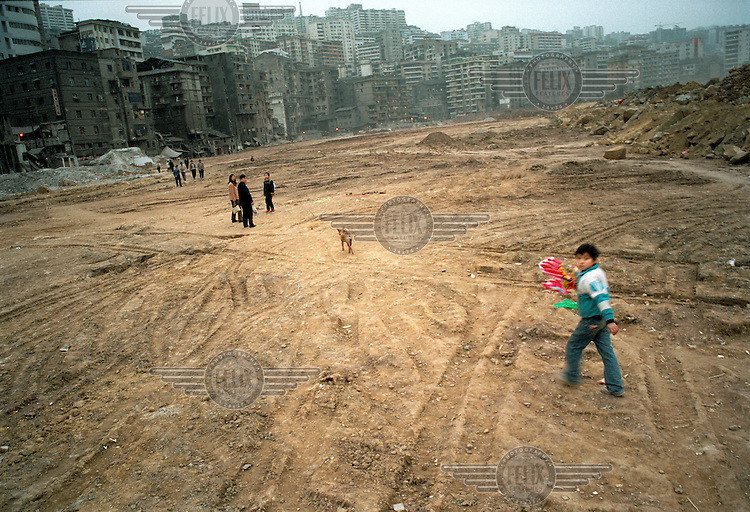 Families walk back to the their homes in the new district on the hillside.  The darker buildings are all that remain of the old city after it was cleared.  The reclaimed land is to protect the rest of the city from the imminent rise in the Yangtze river's water level after the completion of the Three Gorges Dam project.