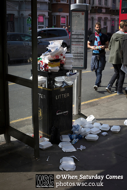 West Ham United 2 Crystal Palace 2, 02/04/2016. Boleyn Ground, Premier League. A litter bin overflowing with rubbish on Green Street near the Boleyn Ground before West Ham United hosted Crystal Palace in a Barclays Premier League match. The Boleyn Ground at Upton Park was the club's home ground from 1904 until the end of the 2015-16 season when they moved into the Olympic Stadium, built for the 2012 London games, at nearby Stratford. The match ended in a 2-2 draw, watched by a near-capacity crowd of 34,857. Photo by Colin McPherson.