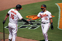 Baltimore Orioles Yolmer Sanchez (13) shakes hands with Trey Mancini (16) after scoring a run during a Major League Spring Training game against the Philadelphia Phillies on March 12, 2021 at the Ed Smith Stadium in Sarasota, Florida.  (Mike Janes/Four Seam Images)