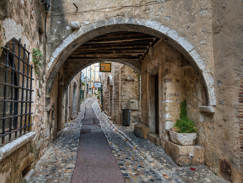 """View of archway and street (the Rue Grande), Saint Paul de Vence, showing the underside of the """"pontis"""", or bridge, connecting buildings on opposite sides of the street."""