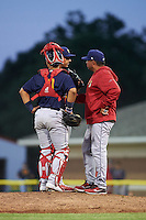 State College Spikes pitching coach Darwin Marrero (39) talks with pitcher Steven Farinaro (19) and catcher Jeremy Martinez (41) during a game against the Batavia Muckdogs on June 24, 2016 at Dwyer Stadium in Batavia, New York.  State College defeated Batavia 10-3.  (Mike Janes/Four Seam Images)
