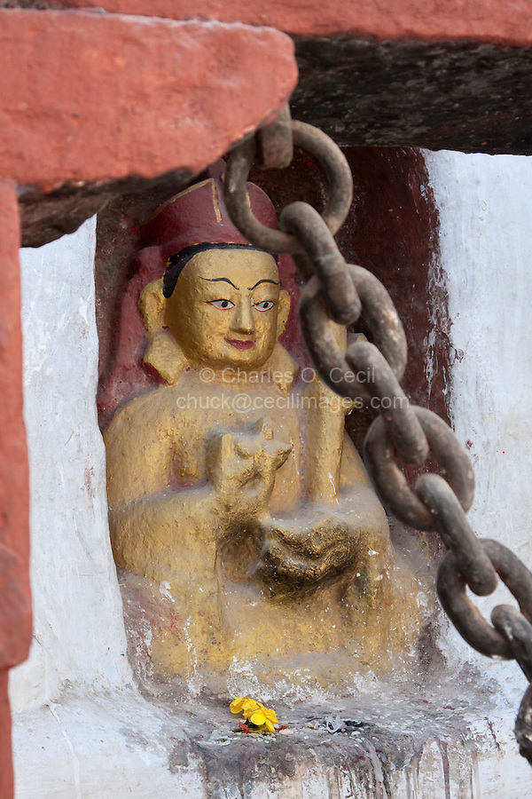 Bodhnath, Nepal.  A Statue of the Buddha adjacent to the Buddhist Stupa of Bodhnath.  The Buddha makes the gesture of turning the wheel of law (the Buddha's teachings) with his right hand, while making the gesture of meditation with the left.
