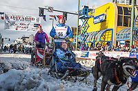 Travis Beals and team leave the ceremonial start line with an Iditarider at 4th Avenue and D street in downtown Anchorage, Alaska during the 2015 Iditarod race. Photo by Jim Kohl/IditarodPhotos.com