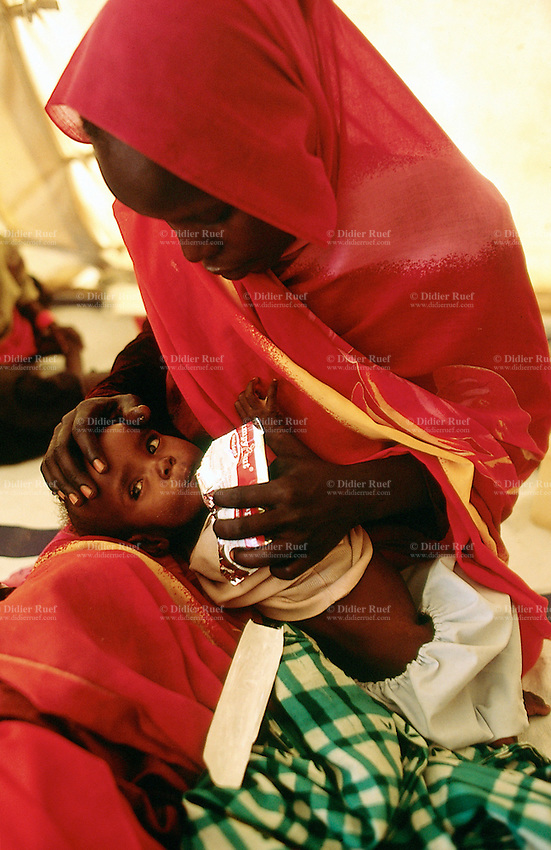Sudan. West Darfur. Habilah. The non-governmental organization (ngo) Médecins sans Frontières (MSF) Switzerland runs an ambulatory therapeutic feeding center (TFC) for malnourished children. A young boy in his mother's arms eats plant peanut. The mother's head is covered by a red veil.© 2004 Didier Ruef