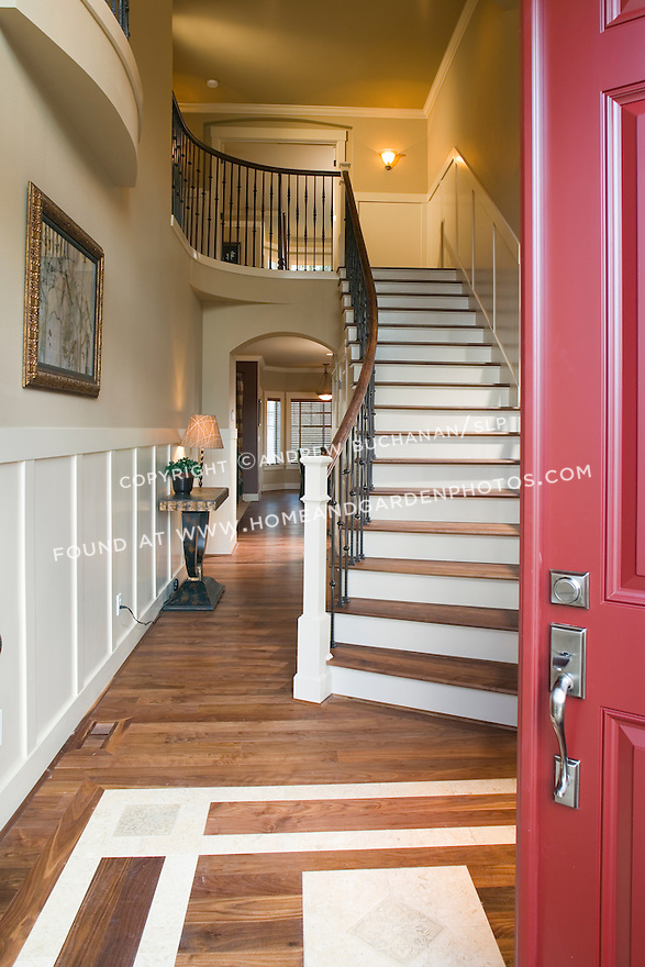 A rich red front door swings open into a dramatic two story 2-story front entry foyer featuring hardwood floors with inlaid tile accents, arched doorways, and a sweeping curved main staircase leading to an upstairs balcony in this contemporary spec home.