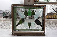scultura costituita da quadrato in legno e bottiglie vuote in vetro