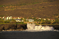 Keauhou golf course along coastline with wave crashing along cliffs and condominiums