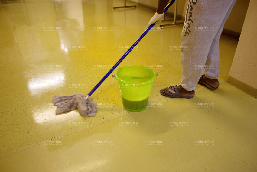 Switzerland. Geneva. A homeless black man from Africa is cleaning the floor in the fallout shelter Richemont. Wet soapy floor. The bunker was constructed as civil defense measures during the Cold War and is a unit of the Civil Protection. Switzerland is unique in having enough nuclear fallout shelters to accommodate its entire population. 7.02.2014 © 2014 Didier Ruef
