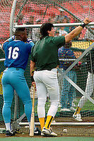 OAKLAND, CA - Jose Canseco of the Oakland Athletics talks to Bo Jackson of the Kansas City Royals near the batting cage during batting practice before a game at the Oakland Coliseum in Oakland, California in 1990. Photo by Brad Mangin