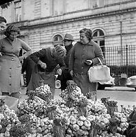 Place du Salin. 15 octobre 1965. Vue d'ensemble de la place avec vendeurs et acheteurs d'ail; au fond bâtiment du tribunal de grande instance.