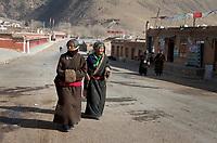 Tibetan women in traditional clothing walk through a small town on the Qinghai-Tibetan Plateau. China.