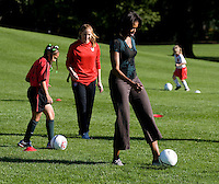 Michelle Obama participates in a drill under the watchful eye of USWNT defender Rachel Buehler during a Lets Move! soccer clinic held on the South Lawn of the White House.  Let's Move! was started by Mrs. Obama as a way to promote a healthier lifestyle in children across the country.