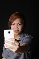 MODEL RELEASED - Asian (Filipino) 17 years old male teenager taking a selfie with his  smart phone