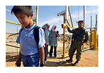 Israeli soldiers open a gate in the security fence to let school children cross the fence, returning from school to their village Jbara, October 28, 2003. The Palestinian village of Jbara was left on the Israeli side of the fence, 88 school children have to cross the new security fence on their way to school on the Palestinian side. Israeli Prime Minister Ariel Sharon defended his country's barrier from the Palestinians against European criticism yesterday, saying it was vital for Israel's security. Photo by Quique Kierszenbaum