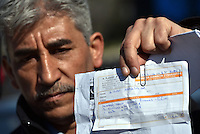 Pictured: A migrant man shows his bus transfer ticket at the refugee camp Tuesday 23 February 2016<br /> Re: Migrants at a refugee camp in the Schisto area of Athens, Greece.
