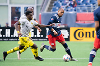 FOXBOROUGH, MA - MAY 16: Derrick Etienne Jr. #22 Columbus SC pressures Teal Bunbury #10 of New England Revolution during a game between Columbus SC and New England Revolution at Gillette Stadium on May 16, 2021 in Foxborough, Massachusetts.