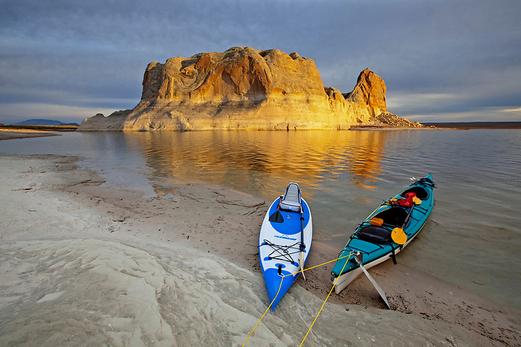 Two kayaks rest on Lake Powell's shoreline as the setting sun illuminates Castle Butte in the Glen Canyon National Recreation Area on the Arizona-Utah border, USA
