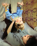 Evan Ross Mendenhall gets a lift from his mother Deborah Jo Bruner Mendenhall in our Fullerton, CA home around 1990 (estimated) in a shoot for Focus on the Family of father's telling bedtime stories to their children which Deborah actually shot after it was set up. This was just for fun. The quilt on the wall was made by Debbie's Mama Cordellia Collier (married to Ross Collier -- Evan's name sake) of St. Charles, Va. The bed spread was crochetted by either Mama or Jim's Mother Lela Laverne (Paul/Mendenhall) Matheny of Indianapolis, IN. The bedspread was one of two exact copies of one another that our family had made for each of us independently. The only difference was that Lela ran out of pure white thread so part of her's was off white.  photo Jim Mendenhall