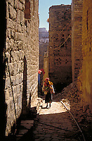 An Arabic man in traditional dress is carrying vegetables as he strolls the narrow, stone street below Thilla's towerhouses. Thilla, Yemen.