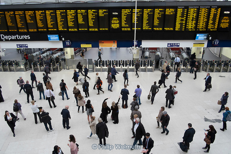 Passengers waiting for trains at London Waterloo station