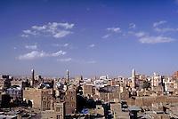 Sana's minaret towers project high above the mud brick buildings. Architecture, religion, mosque, Islam, city, cities,. Sana, Yemen.