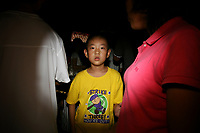 CHINA. Beijing. A young boy amongst people watching the opening ceremony of the Beijing 2008 Summer Olympics. 2008
