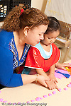 Education preschool 3-4 year olds art activity play dough female teacher working one on one with girl helping her to count pointing at pieces of play dough vertical