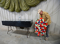 Don Seaman, a volunteer at the Arkansas Air and Military Museum in Fayetteville, positions a flower arrangement Tuesday, Jan. 5, 2021, as he and others build a display in honor of G. Leonard McCandless beneath a parachute inside the museum. McCandless is the founder of the museum and died Saturday at 82. McCandless made more than 2,100 jumps with the 82nd Airborne Division and later as founder of the Arkansas Falling Stars Skydiving Team, jumping at events in Northwest Arkansas. Visit nwaonline.com/210106Daily/ for today's photo gallery. <br /> (NWA Democrat-Gazette/Andy Shupe)