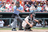 Home plate umpire Joseph Born makes a call behind catcher Bryan Holaday #12 in a game between the Erie SeaWolves and Harrisburg Senators at Jerry Uht Park on August 7, 2011 in Erie, Pennsylvania.  Harrisburg defeated Erie 6-1.  (Mike Janes/Four Seam Images)