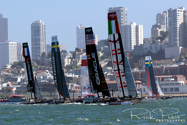 Americas Cup boats race along the San Francisco waterfront.
