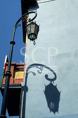Buenos Aires, Argentina. Ornate old fashioned street lamp and its shadow on the wall of a building with a balcony. La Boca.