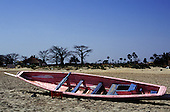 The Gambia. Small boat on a beach with trees in silhouette and a thatched hut.