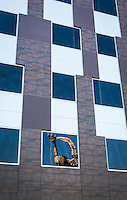 "The raised arms and head of the ""Truth is Beauty"" sculpture is reflected in a window of the San Leandro Tech Campus."