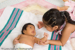 newborn baby girl one month old  Mexican American lying on back in diaper interaction with older sister age 3 horizontal