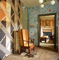Albion House near Bath, the home of decorative painter Adam Calkin. An entrance hall with a stone floor and patterned paint finish on the walls, leading to a sitting room.
