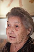 Switzerland. Canton Ticino. Sala. Elsy (Elsa) Hofer Ferrari Ramuz is 86 years old. She seats on a sofa in her living room. Elsy Hofer Ferrari Ramuz is the niece of Charles-Ferdinand Ramuz (September 24, 1878 – May 23, 1947) who was a French-speaking Swiss writer. 14.11.2017 © 2017 Didier Ruef
