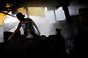 A woman evenly spreads to wood on the oven for cooking the charcoal in the slums of Smokey Mountain-II in Manila in Philippines. Photo: Sanjit Das