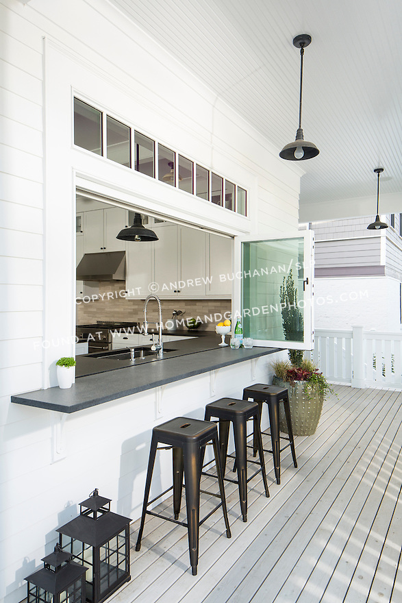 A folding glass kitchen window and bar area with outdoor stools merge the inside and outside in this beautiful home.
